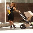 Stock Photo: Fashionable modern mother on city street with pram. Young mo