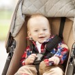Stock Photo: Beautiful little smiling baby in baby carriage on streets
