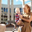 Trendy modern mother on a city street with a pram. Young mother — Stock Photo #38547151