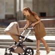 Trendy modern mother on a city street with a pram. Young mother — Stock Photo