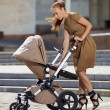 Fashionable modern mother on a urban street with a pram. Young m — Stock Photo #38547339