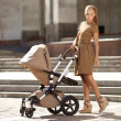 Stock Photo: Fashionable modern mother on urbstreet with pram. Young m