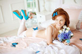 Beautiful woman lying on the bed with flowers — Stock Photo