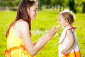 Mother feeds baby outdoors in the grass — Stock Photo