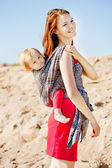 Beauty woman with a baby in a sling. Mom and baby. Mother and ch — Stock Photo
