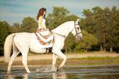 Young woman on a horse. Horseback rider, woman riding horse on b — ストック写真