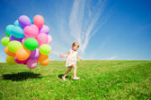 Little girl holding colorful balloons. Child playing on a green — 图库照片