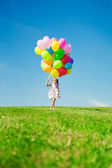 Little girl holding colorful balloons. Child playing on a green — Stock Photo