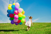 Little girl holding colorful balloons. Child playing on a green — Stockfoto