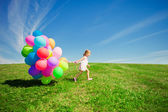 Little girl holding colorful balloons. Child playing on a green — Stok fotoğraf