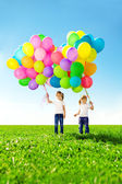 Ballons colorés de little girl holding. enfant jouant sur un green — Photo