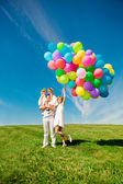 Happy family holding colorful balloons. Mom, ded and two daughte — ストック写真