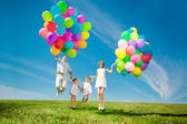 Happy family holding colorful balloons outdoor. Mom, ded and two — Stock Photo