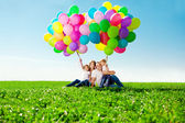 Happy family holding colorful balloons. Mom, ded and two daughte — Photo