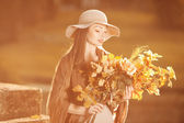 Young woman walking in autumn park with a bouquet of fall leav — Stock Photo