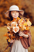 Young fashion woman walking in autumn park with a bouquet of fa — Stock Photo
