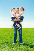 Happy family in outdoor park at sunny day. Dad and two daughter — Stock Photo