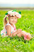 Beautiful little girl with a rose in his hand and a wreath of ro — Stock Photo