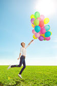 Young woman with balloons in hands in the field against the sky — Stock Photo