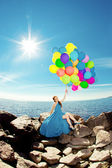 Luxury fashion woman with balloons in hand on the beach against — Stock Photo
