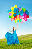 Luxury fashion woman with balloons in hand on the field against — Stock Photo