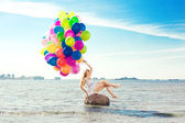 Beautiful young stylish woman with multi-colored rainbow balloon — Stock Photo