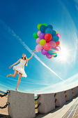 Happy birthday woman against the sky with rainbow-colored air ba — Stock fotografie