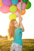 Happy birthday woman against the sky with rainbow-colored air ba — Stockfoto