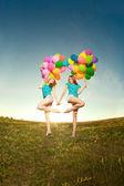 Grattis på födelsedagen kvinnor mot himlen med rainbow-färgade luft ba — Stockfoto