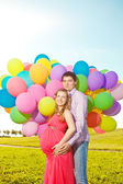Young healthy beauty pregnant woman with her husband and balloon — Stock Photo