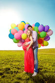 Young healthy beauty pregnant woman with her husband and balloon — Zdjęcie stockowe