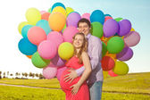 Young healthy beauty pregnant woman with her husband and balloon — Stok fotoğraf