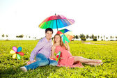 Young healthy beauty pregnant woman with her husband and rainbow — Stok fotoğraf