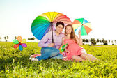 Young healthy beauty pregnant woman with her husband and rainbow — Stock fotografie