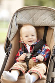 Beautiful little smiling baby in a baby carriage on the streets — Stock Photo