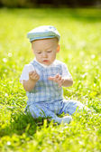 Cute little baby in the park on the grass. Sweet baby outdoors. Smiling emotional kid on a walk. Smile of a child — Stock Photo
