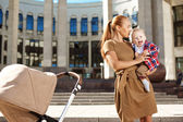 Fashionable modern mother on a city street with a pram. Young mo — Foto de Stock