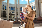 Fashionable modern mother on a urban street with a pram. Young m — Stock Photo