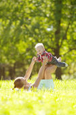 Cute little baby in the park with mother on the grass. Sweet bab — Zdjęcie stockowe