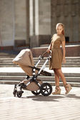 Fashionable modern mother on a urban street with a pram. Young m — 图库照片