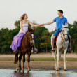 Two riders on horseback at sunset on the beach. Lovers ride hors — Stock Photo #46338645