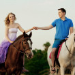 Two riders on horseback at sunset on the beach. Lovers ride hors — Stock Photo #46338673