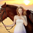 Beautiful woman riding a horse at sunset on the beach. Young gir — Stock Photo #46339097