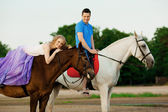 Two riders on horseback at sunset on the beach. Lovers ride hors — Stock Photo
