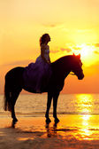 Beautiful woman riding a horse at sunset on the beach. Young gir — Stock Photo