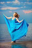 Mujer de lujo en un vestido de noche largo azul en la playa. belleza — Foto de Stock