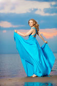 Luxury woman in a long blue evening  dress on the beach. Beauty  — Stock Photo