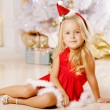 Beautiful little Santa girl near the Christmas tree.  Happy girl — Stock Photo #46349873
