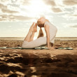 Young beautiful slim woman practices yoga on the beach at sunris — Stock Photo #46340785