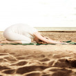 Young beautiful slim woman practices yoga on the beach at sunris — Stock Photo #46340815